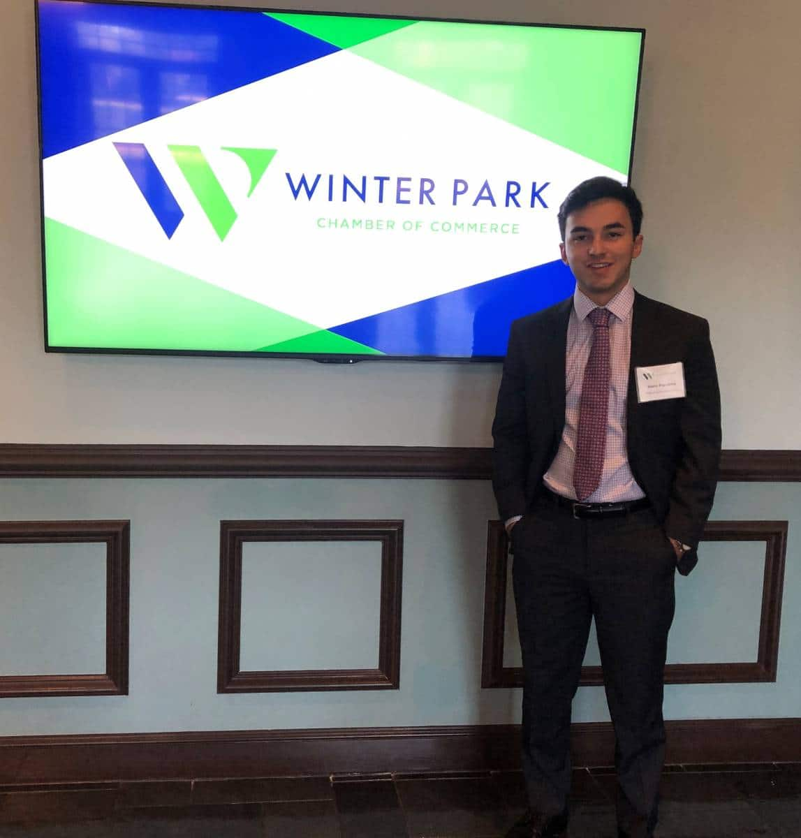 Gabriel Figueroa stands in front of the Winter Park Chamber of Commerce logo