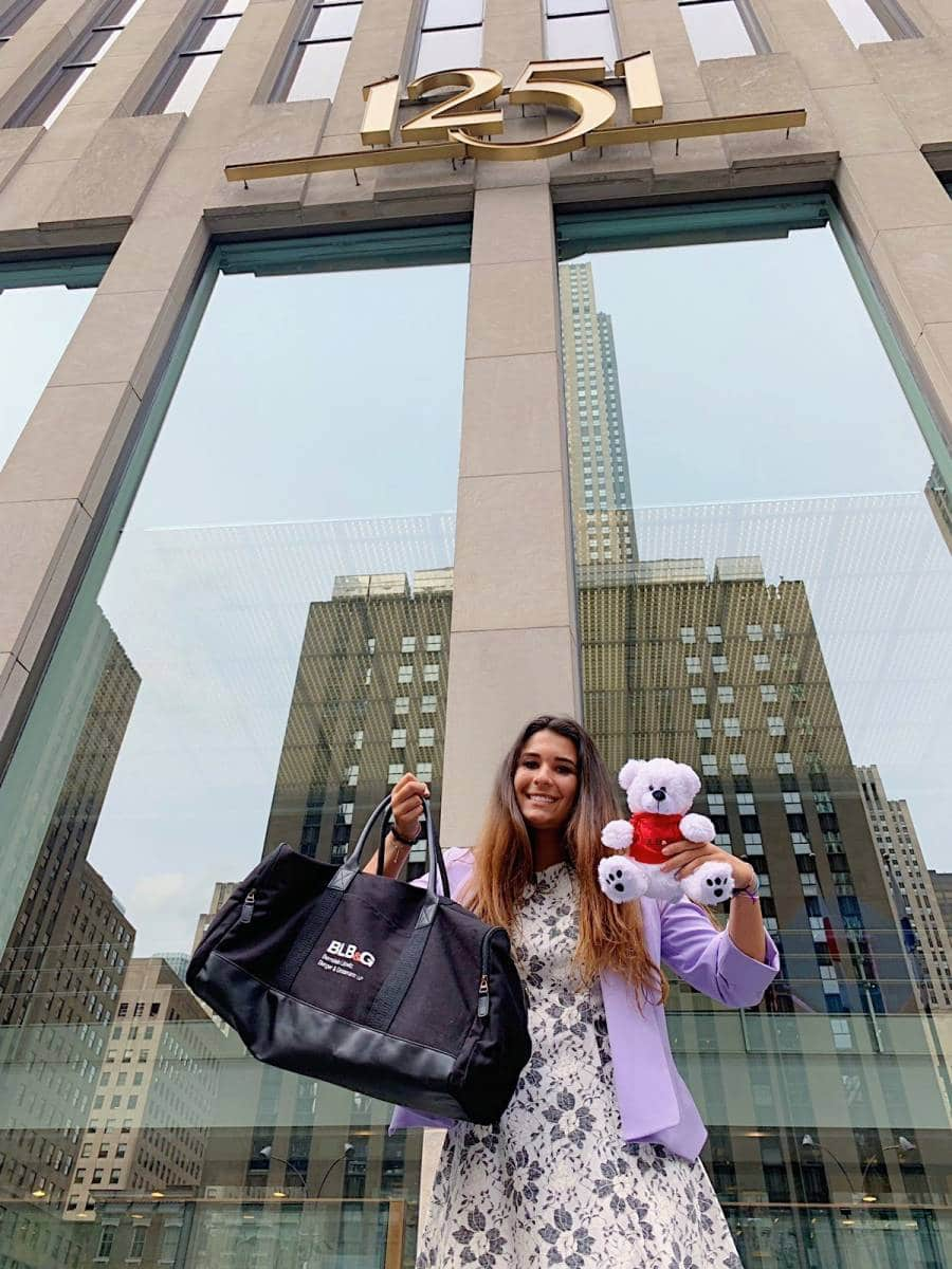 Jessica Lorenzo stands in front of a building in New York City holding a bag and teddy bear