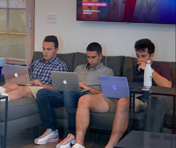 Kyle Finkel sits in front of a computer with two other interns on a couch