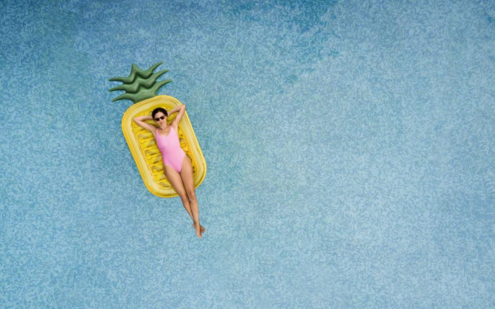 Carefree woman on inflatable pineapple