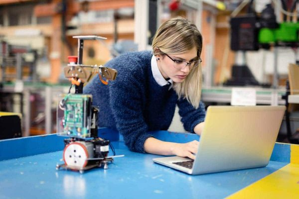 Young woman engineer working on robotics project using laptop