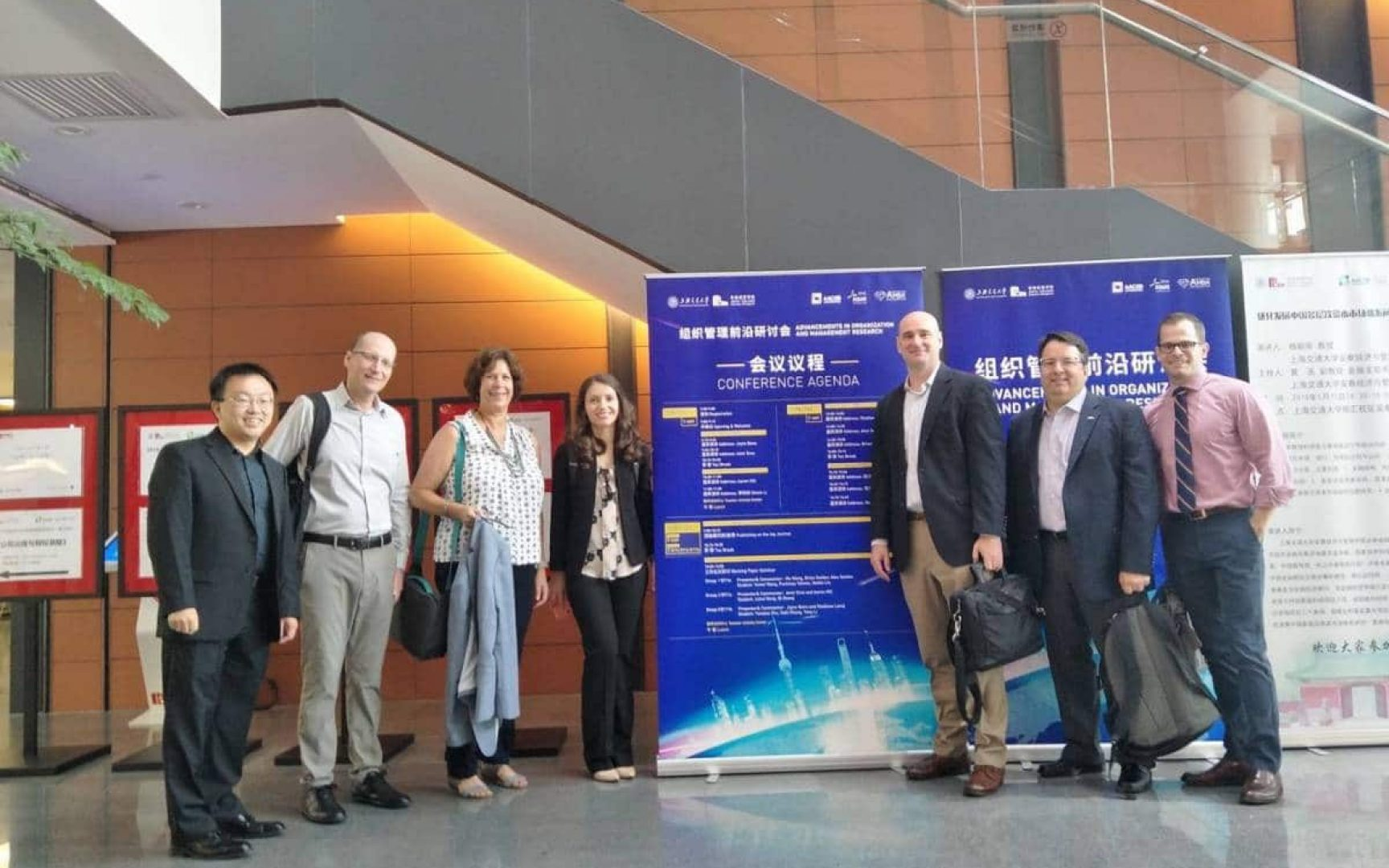 Seven faculty members from Warrington's management department pose in front of the conference sign in China
