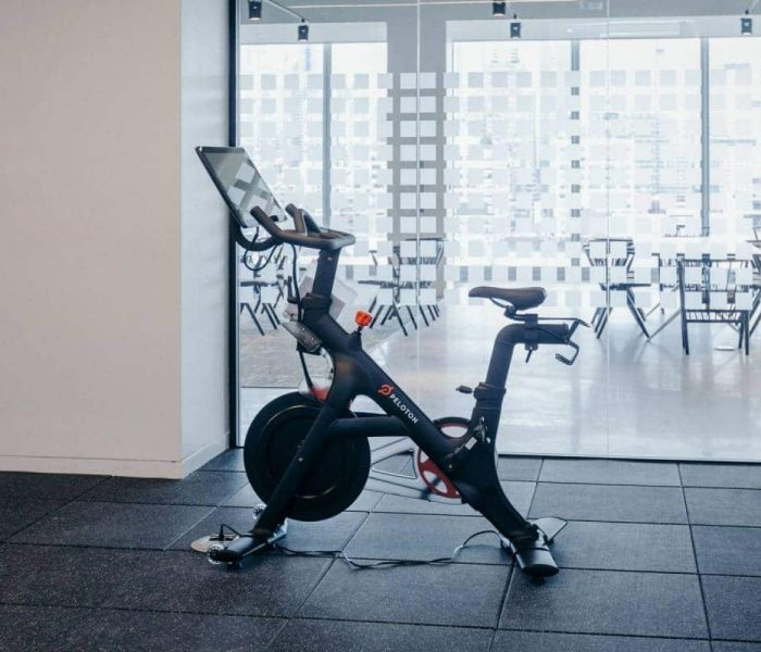 Peloton cardio machine sits in front of a glass window