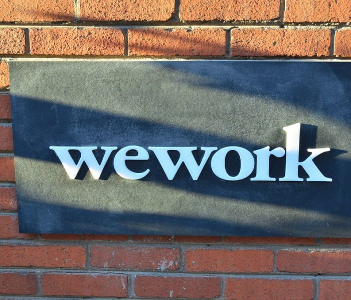 WeWork logo on a sign on a brick wall