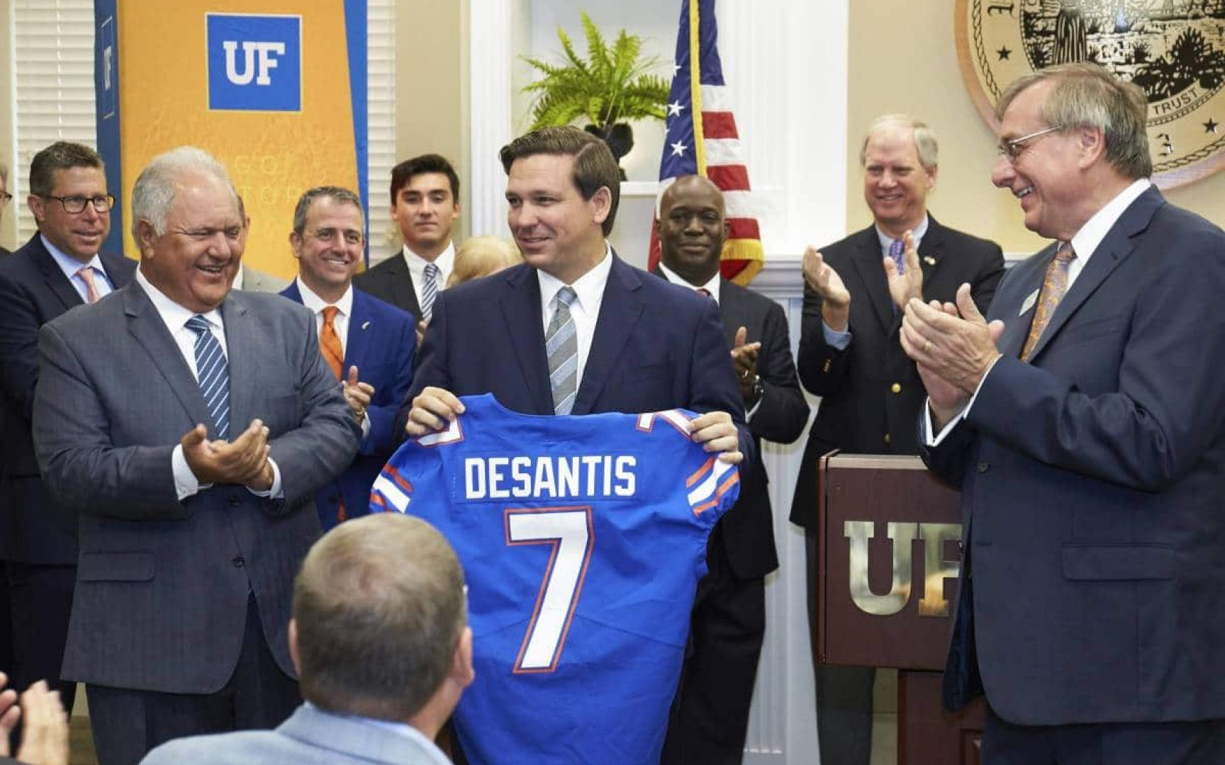 Florida Governor Ron DeSantis holds up a UF football jersey with his last name and the number 7. He is flanked by More Hossini and UF President Kent Fuchs who are clapping