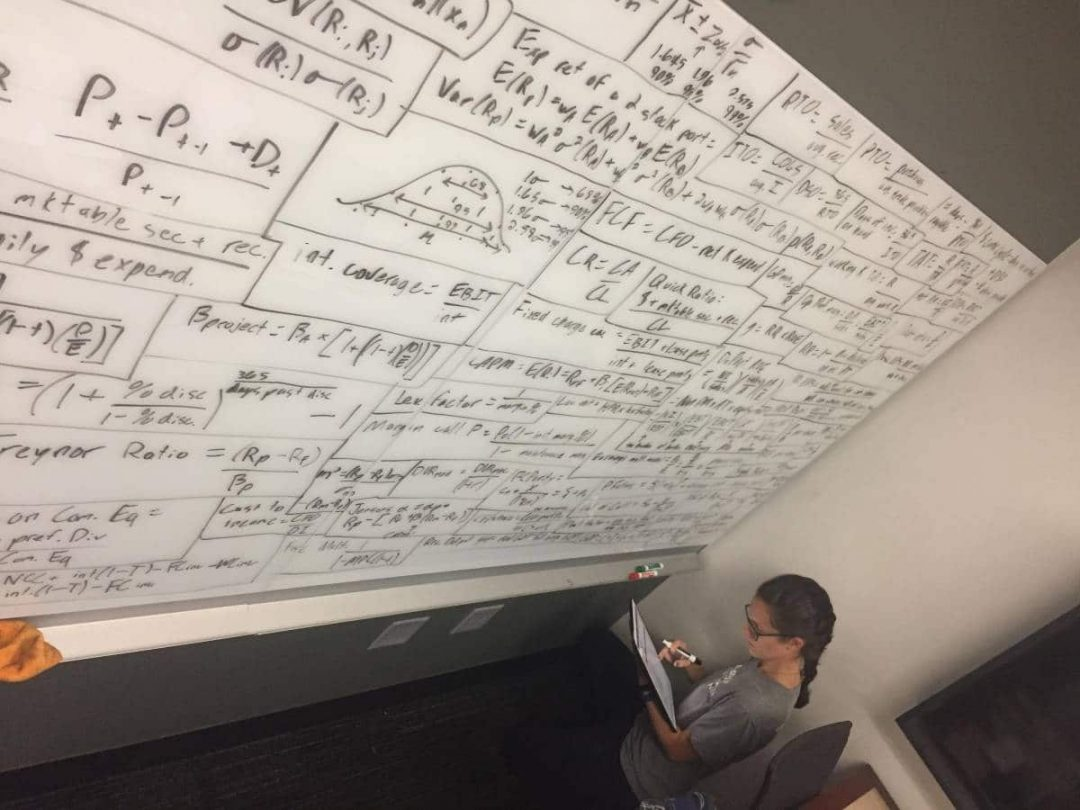 Student looking at a large white board filled with financial equations