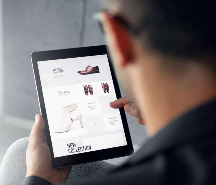 Male hand is browsing an online shop on digital tablet which is selling shoes.