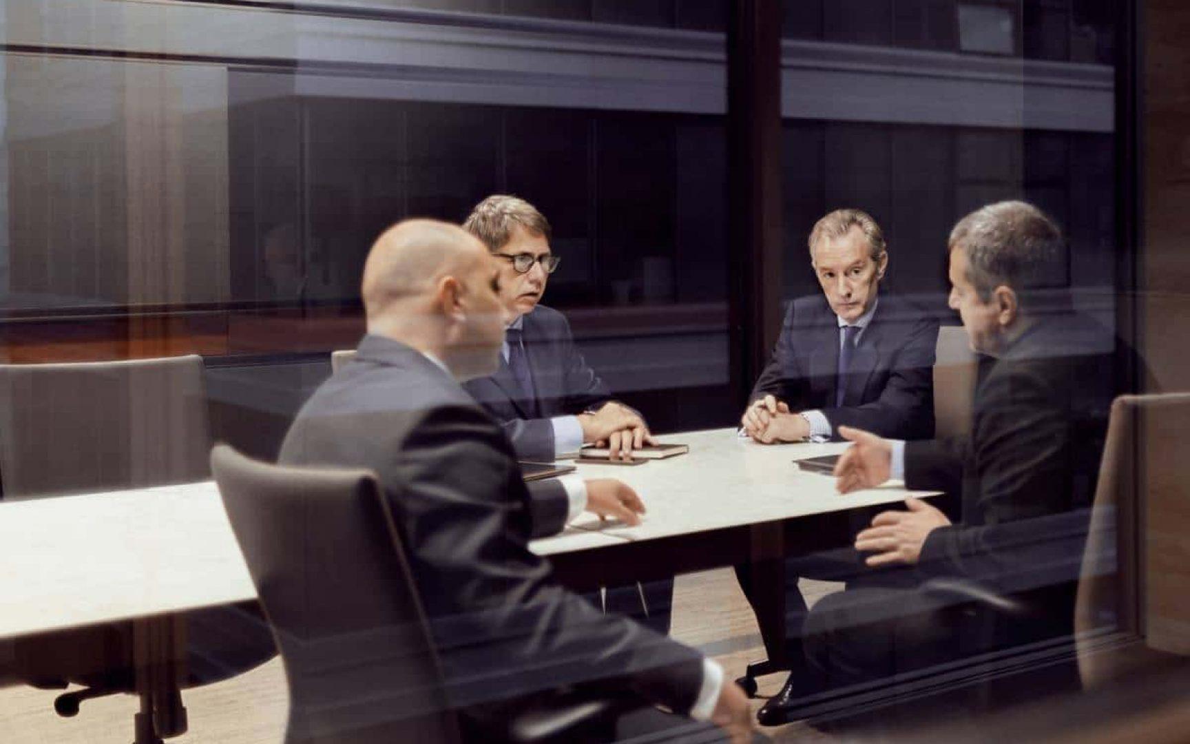 Executive businessmen talking in a dark meeting room