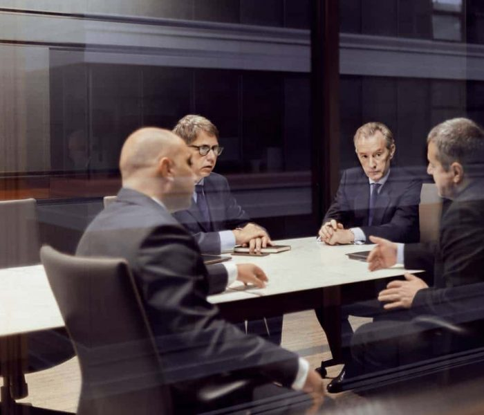 Executive businessmen talking in a dark meeting room