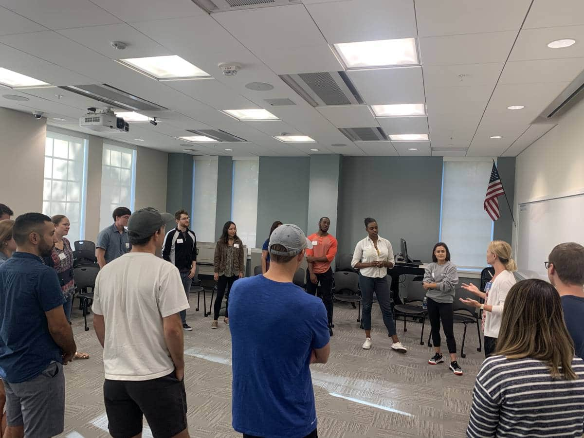 Group of UF MBA students standing in a circle receiving instruction on participating in a group exercise during Transformation Weekend