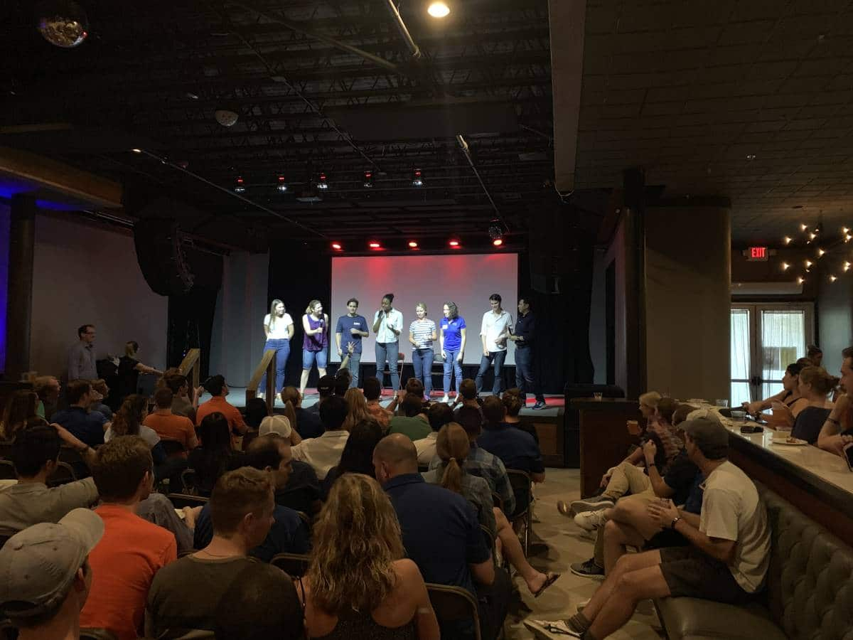 Seven UF MBA students on stage in front of a large crowd at Transformation Weekend