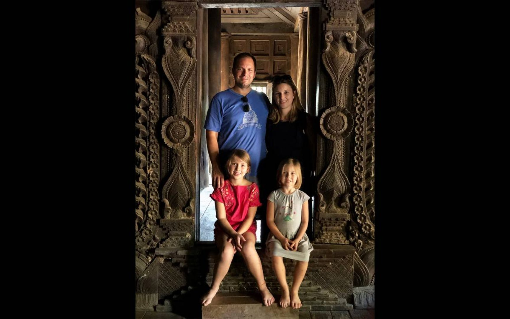 Aaron and Carly Topol pose for a photo in a old building in China with their two daughters