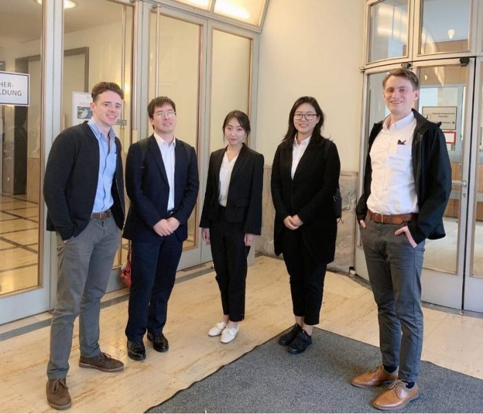 Five students pose for a photo inside the lobby of a building