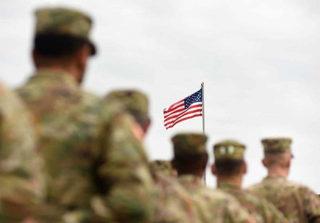 American Soldiers standing below US Flag
