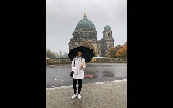 Luiza Duarte stands with an umbrella in historic Berlin