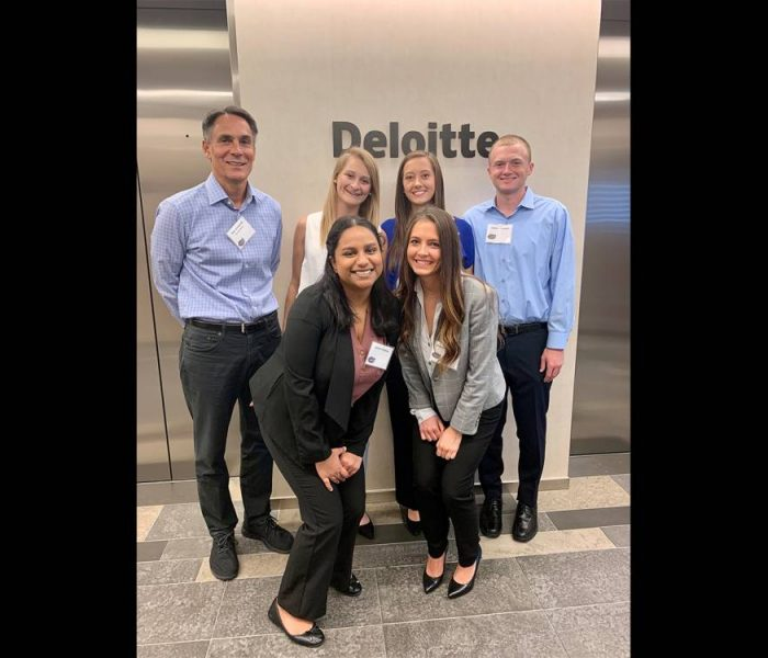 Five students and their faculty advisor pose for a photo at Deloitte