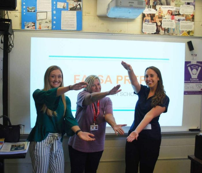 Three women stand in front of a projection screen doing the Gator Chomp
