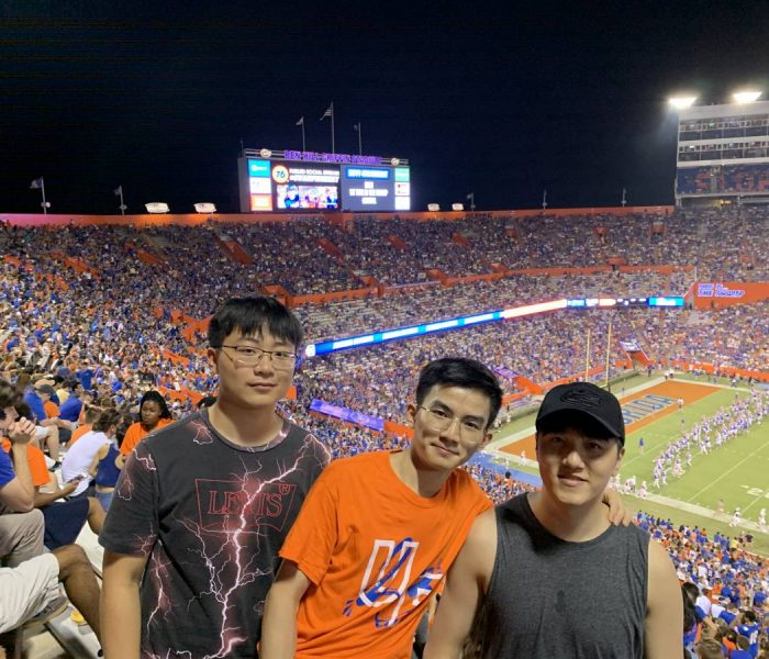 Three Asian students stand up for a photo during a football game in a crowded stadium.