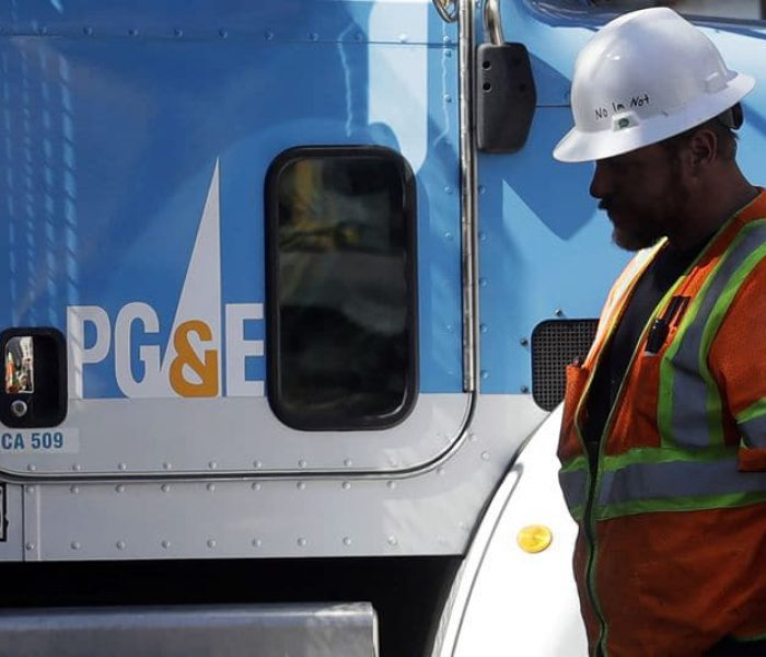 A worker with PG&E stands next to a PG&E utility truck