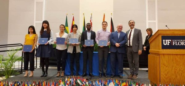 Six students stand with awards alongside two international programs directors