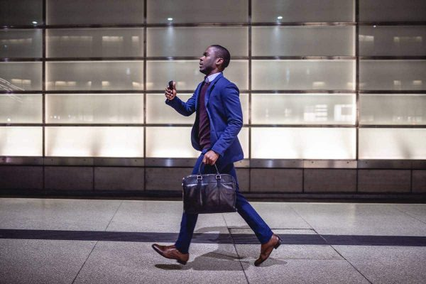 Successful young businessman walking quickly