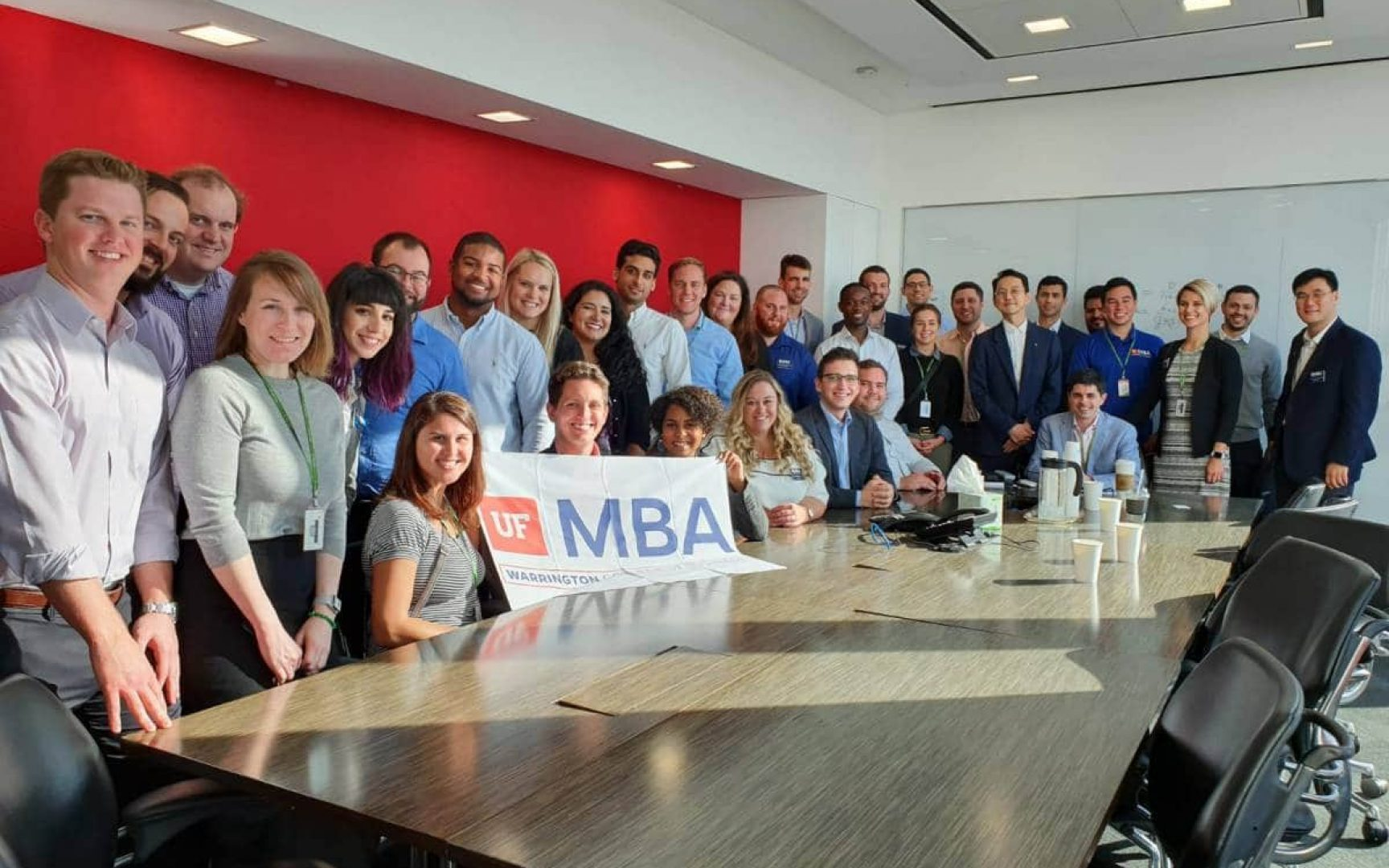 UF MBA students at a large conference table with a UF MBA banner