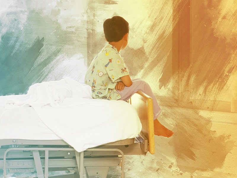 A child sits at the end of a hospital bed