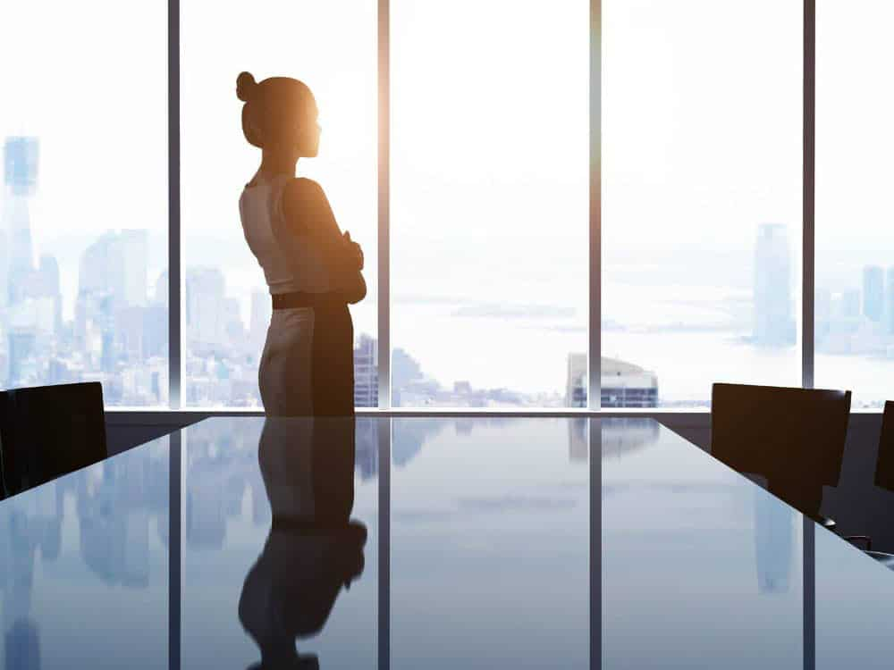 A business woman looks out the window from an empty conference room at the city outside