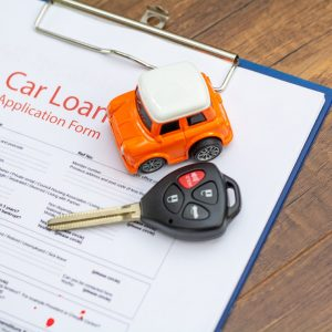 Car keys, car model on the signed agreement document, Buying & Selling car concept