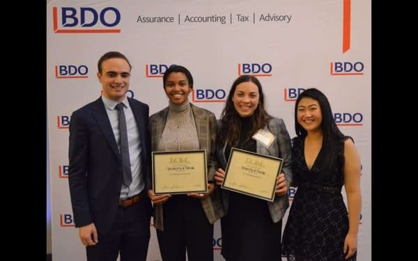 Four students, two from UF Warrington, holding their awards at the ICBC