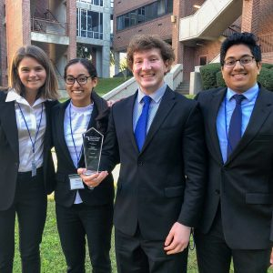Four students in business suits pose with their glass trophy from an ethics case competition