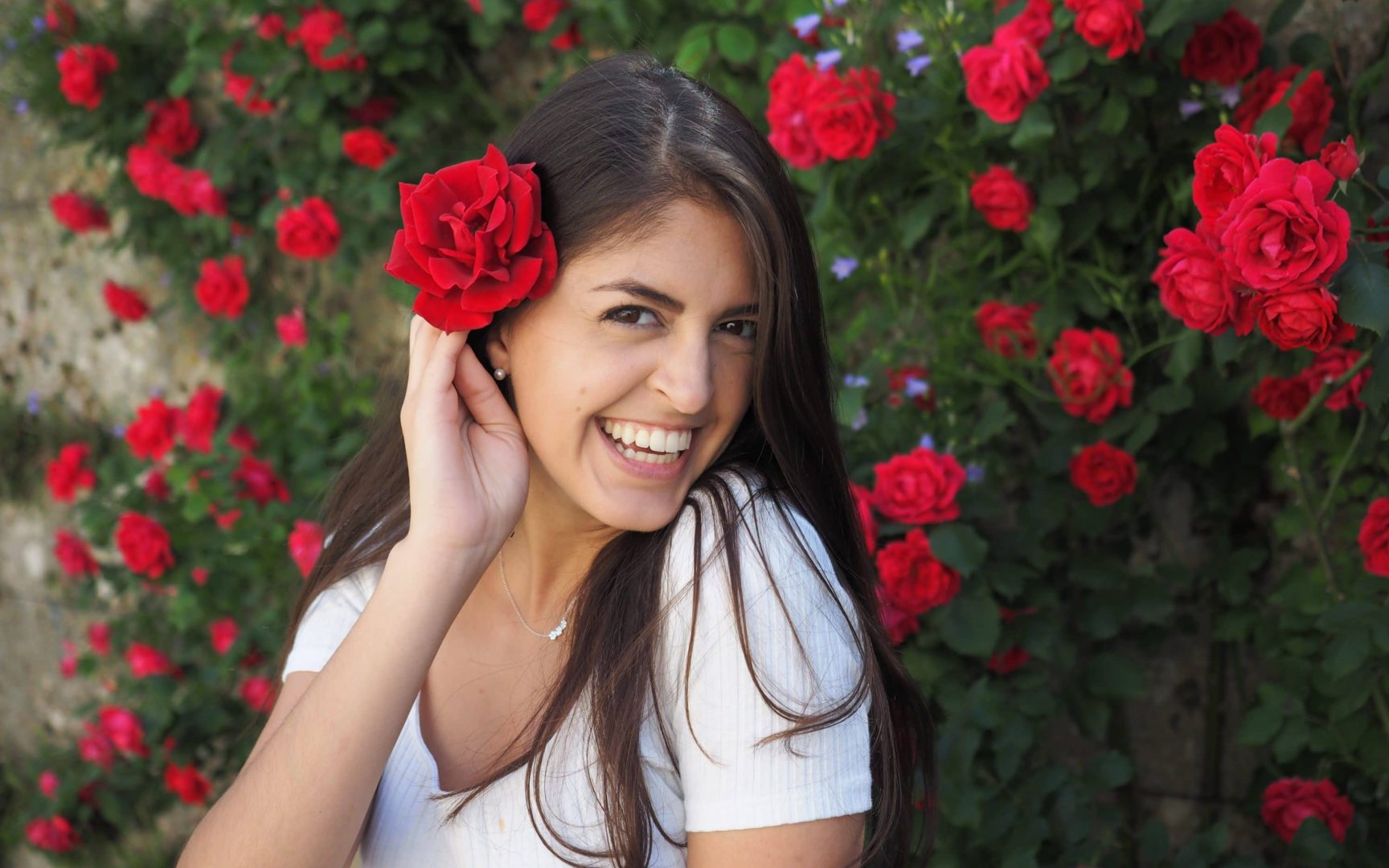 Abbigail Halem in front of a rose wall with a rose in her hair