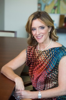 Alison Rand sits at a boardroom table