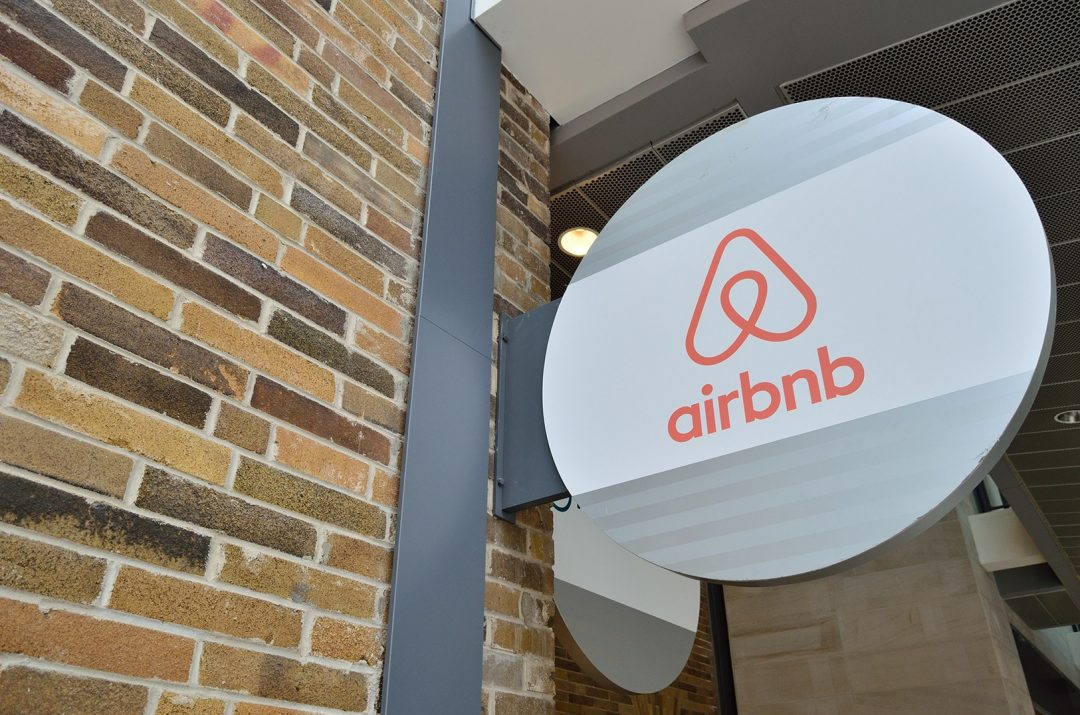 Circular sign with airbnb triangle logo mounted on a brick wall outside