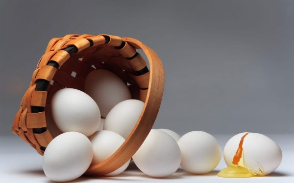 A small brown basket turned on its side with white eggs falling out. One of the eggs is broken.