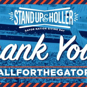 Mr. Two Bits holding a sign in Ben Hill Graiffin stadium with blue tint. Text over the image reads Sand Up and Holler Thank you! #AllfortheGators