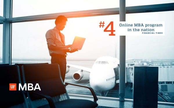 Man standing at an airport with a plan in the background looking at a laptop. Text over image reads #4 Online MBA Program Financial Times