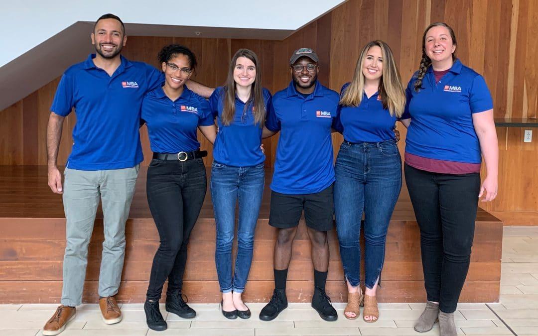 Xavier Balerdi, Sandra Rayo Orozco, Mikaela Medeiros, Vladimir Charles, Alyssa Forbess and Nicole Howe pose for a photo in their UF MBA blue polos.