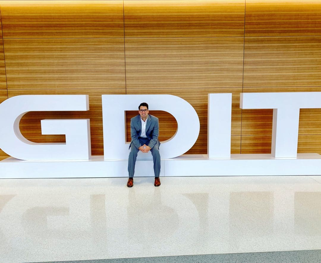 NIck Tharp sits in a large logo for GDIT