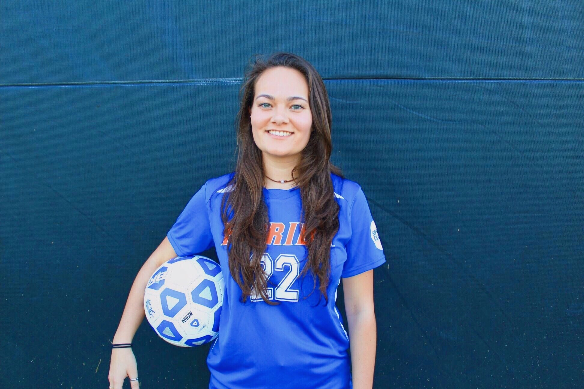 Jenna Griffiths wears a UF soccer jersey and holds a soccer ball under her arm