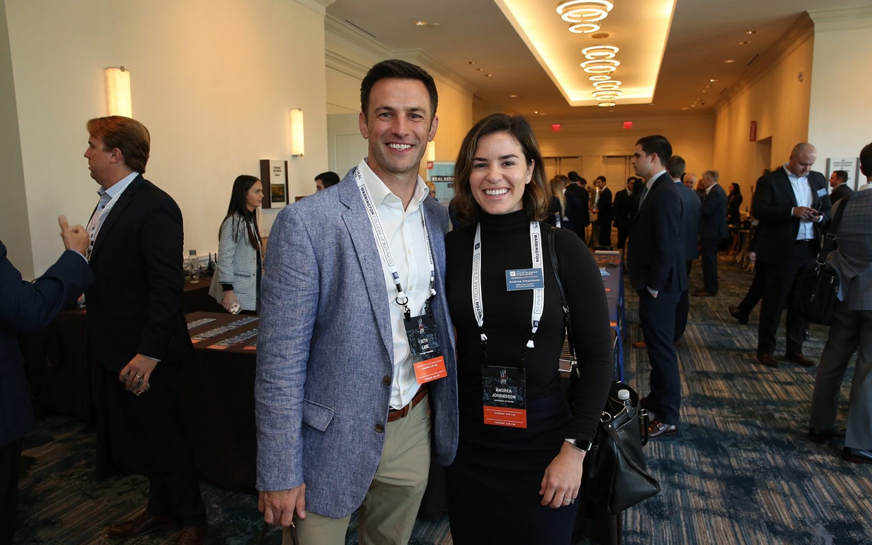 Man in suit poses with woman in suit at a conference