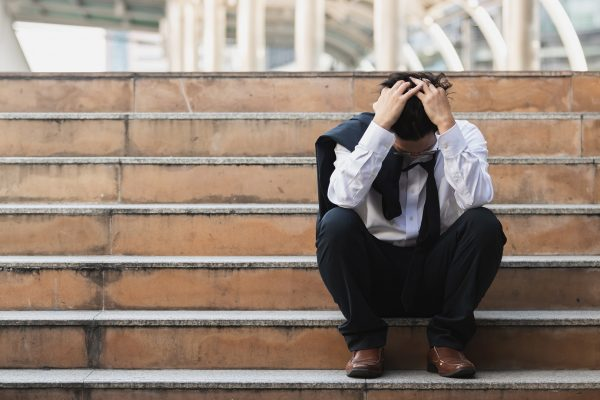Upset stressed young business man in suit with hands on head sitting on stairs.