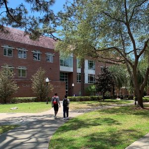 Students walk in front of Gerson Hall on a sunny day