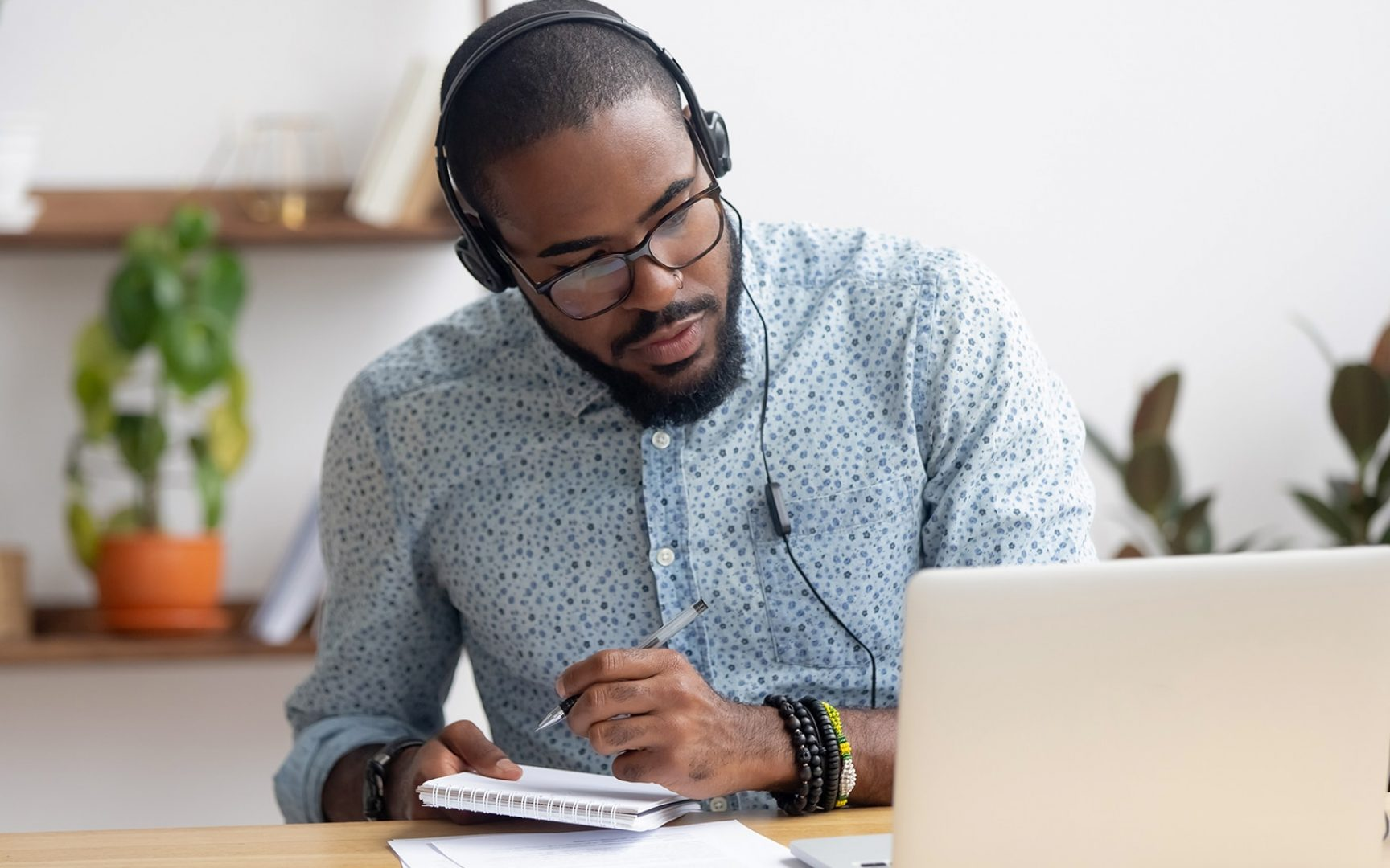 Focused african business man in headphones writing notes in notebook watching webinar video course, serious black male student looking at laptop listening lecture study online on computer e learning