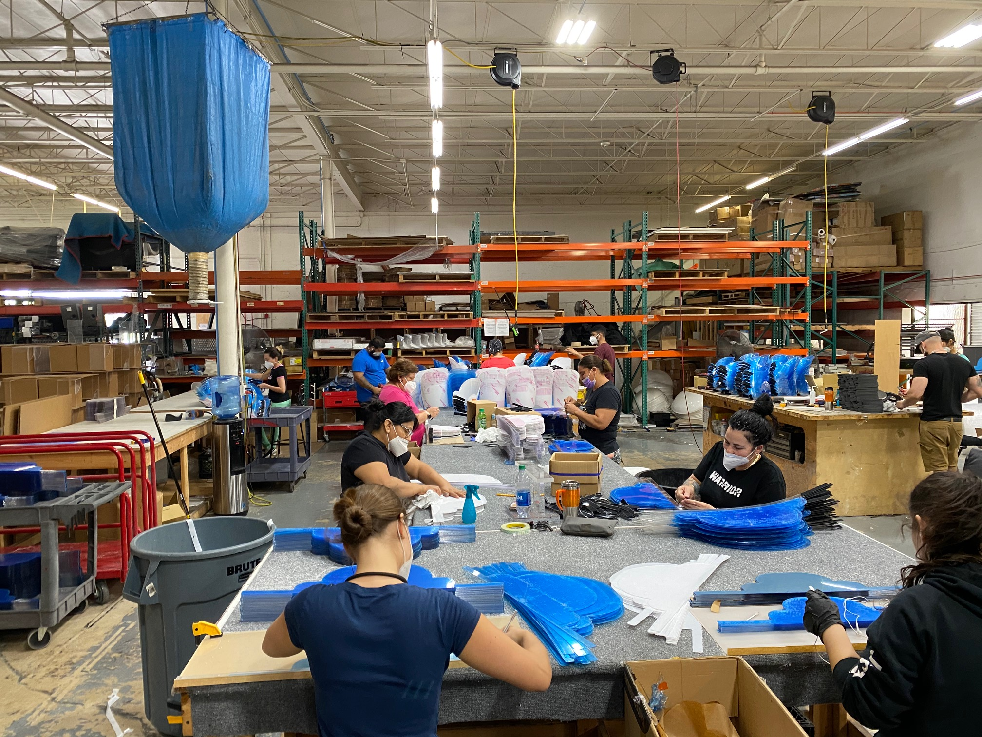 Wide-view of a warehouse of workers producing plastic face shields