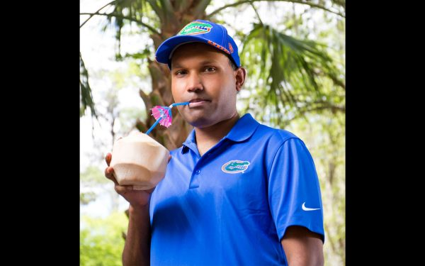 Cocovana founder Sheldon Barrett, wearing a blue Gator shirt and hat, drinks out of a coconut through a straw with an umbrella.