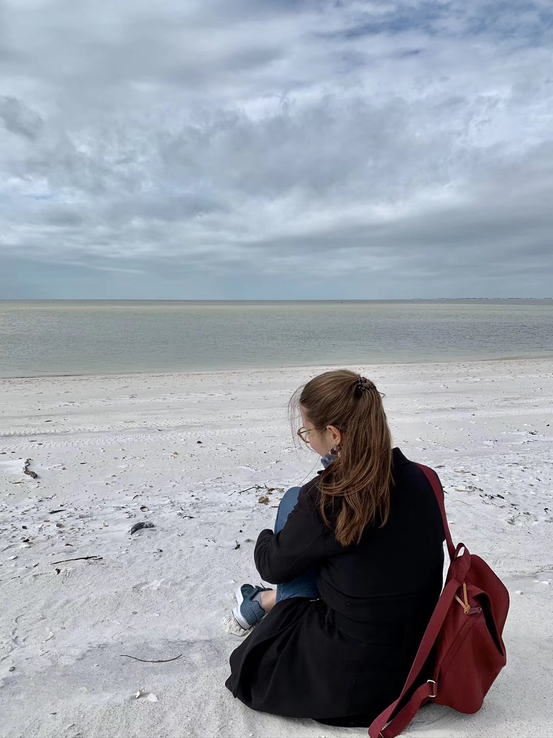 Johanna Pallmann looks out at the water while sitting on the beach.