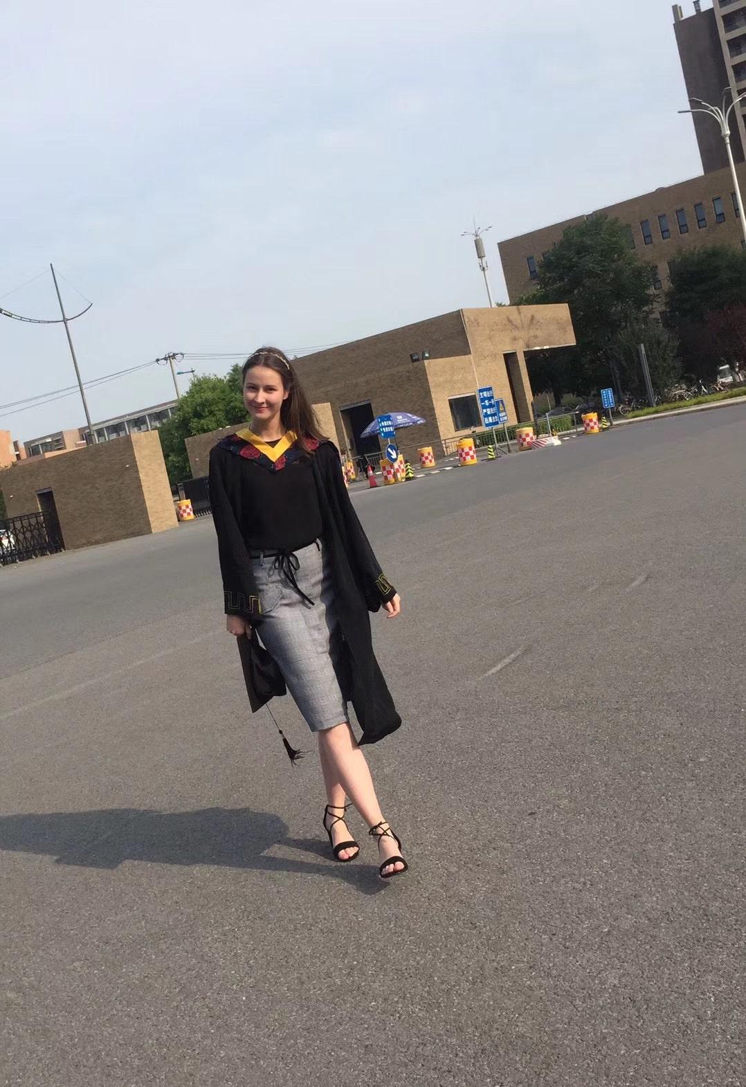 Johanna Pallmann walks towards the camera in a graduation robe
