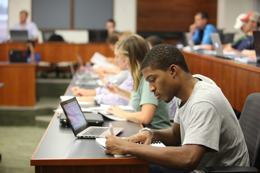 Side view of a row of students looking down while taking notes in class