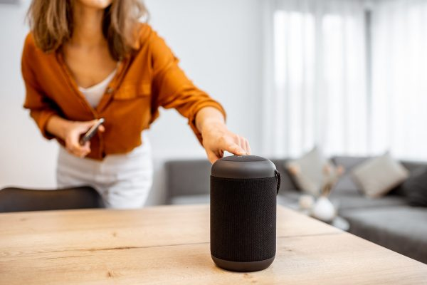 Young woman turning on wireless smart column at home. Concept of a smart home wireless devices. Concept of smart home and voice command control